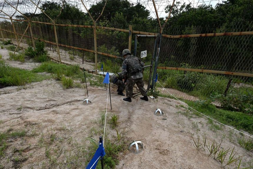 This handout photo taken on Aug 9, 2015 and released on Aug 10, 2015 by the South Korean Defence Ministry shows South Korean soldiers inspecting the scene where planted landmines exploded on Aug 4, maiming two soldiers on border patrol in the Demilit