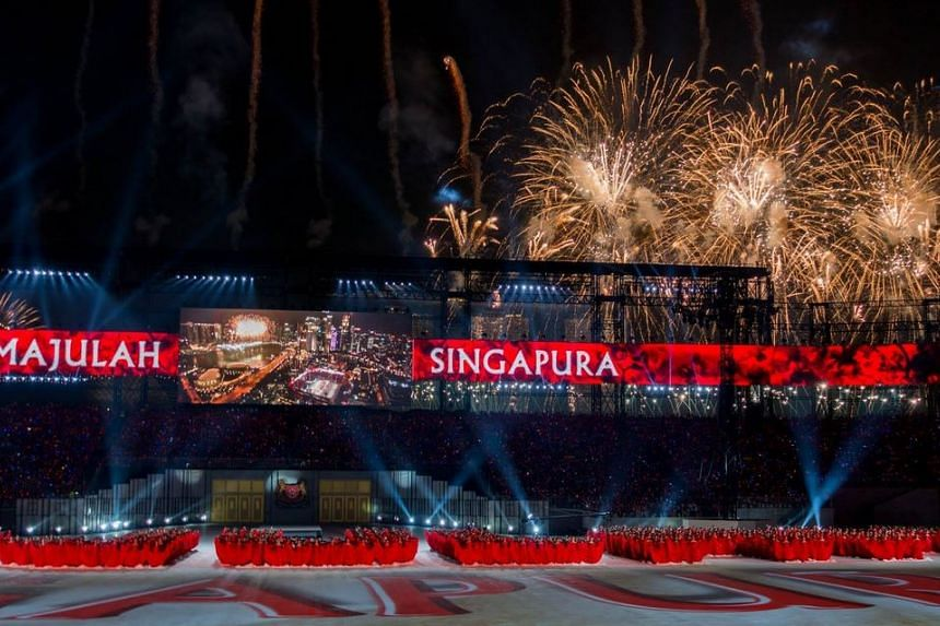 An overall view of the parade arena, complete with fireworks in the background.