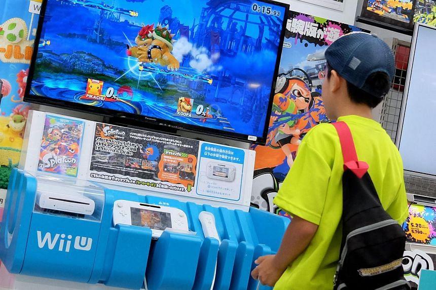 A boy plays a video game at an electronics retail shop.