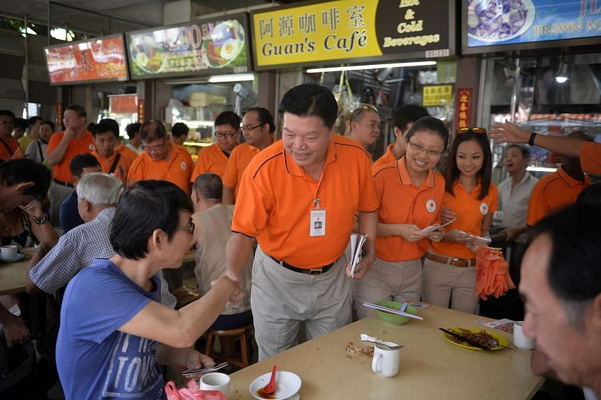 Sebastian Teo (left), president of the National Solidarity Party (NSP), greets MacPherson residents at the Circuit Road Block 89 Food Centre on Aug 2, 2015.