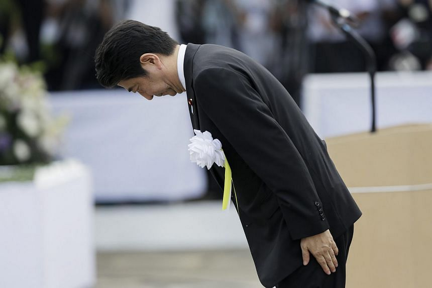 Japanese Prime Minister Shinzo Abe bows in front of the Peace Prayer statue before delivering a speech during the during the 2015 Nagasaki Peace Ceremony at the Nagasaki Peace Park, in Nagasaki, southwestern Japan, on Aug 9, 2015.