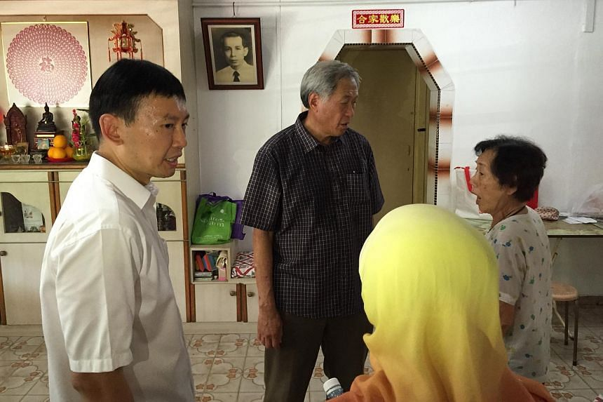 Defence Minister Ng Eng Hen (second from left) who was on a walkabout visiting residents in Jalan Dusun being accompanied by outgoing Second Permanent Secretary for Trade and Industry Chee Hong Tat (left).