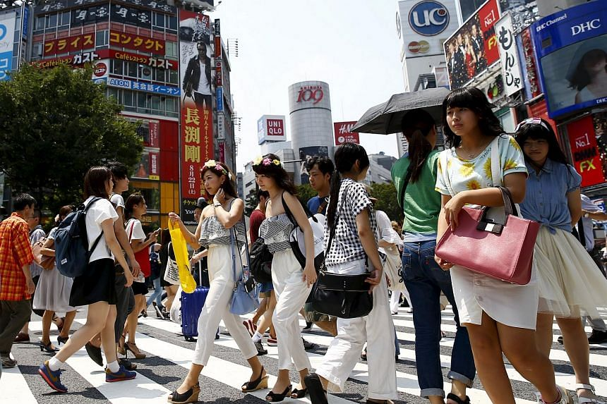 People cross a junction in front of advertising billboards in the Shibuya shopping district in Tokyo.