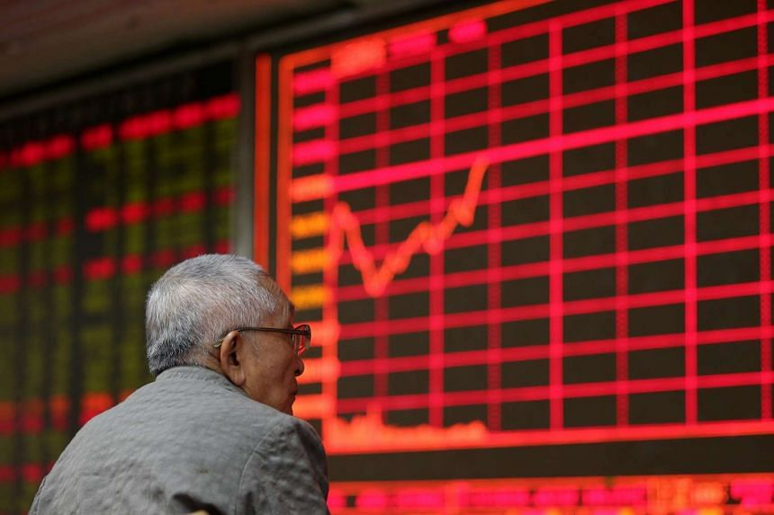 A stock investor watches an electronic screen showing the stock composite index at a brokerage house in Beijing, China.