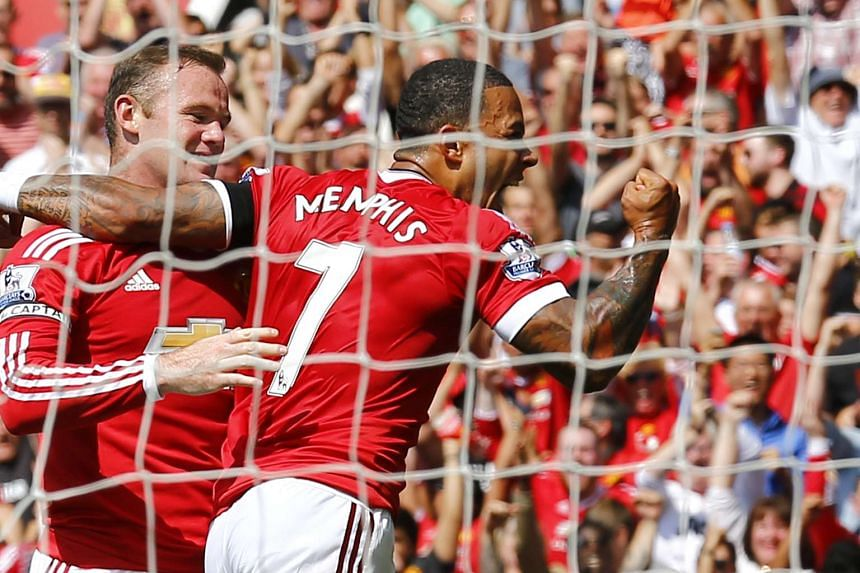 Memphis Depay (right) and Wayne Rooney (left) celebrate after Tottenham's Kyle Walker scored an own goal and the first goal for Manchester United on Aug 8, 2015.