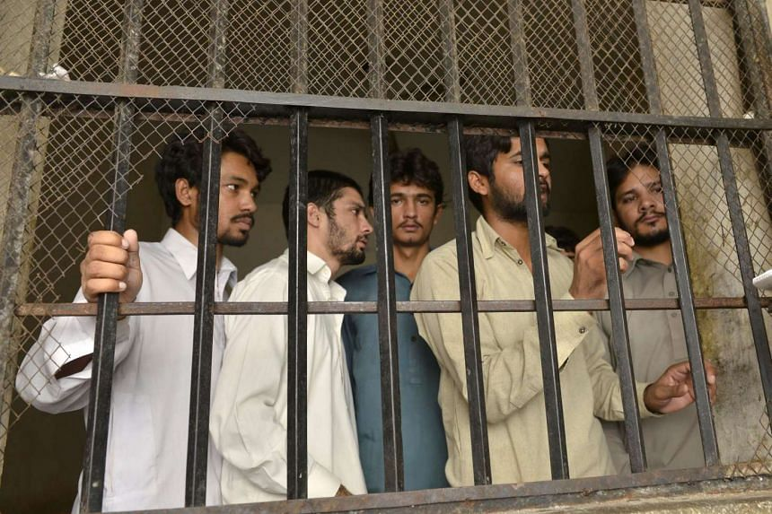 Arrested gang members of a sexual abuse scandal stand in the police lockup in Hussain Khan Wala village, Pakistan, on Aug 9, 2015.