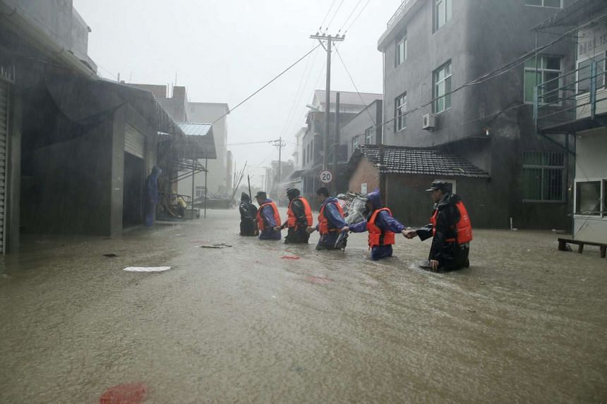 Paramlitary policemen walk hand in hand in flooded Chengli village in Ningde, south-east China's Fujian province, on Aug 9, 2015.