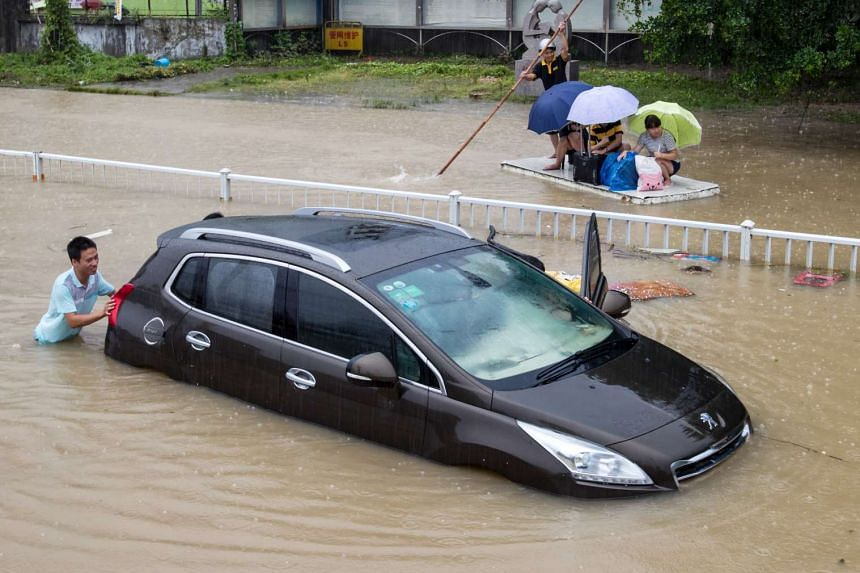 A trapped car is pushed along a flooded street after Typhoon Soudelor hit Fuzhou, Fujian province, China, on Aug 9, 2015.
