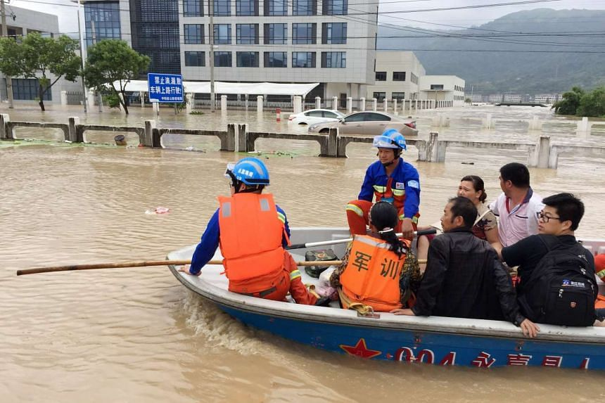 Rescuers working in the flooded Mabu township in Pingyang county in east China's Zhejiang province on Aug 9, 2015.