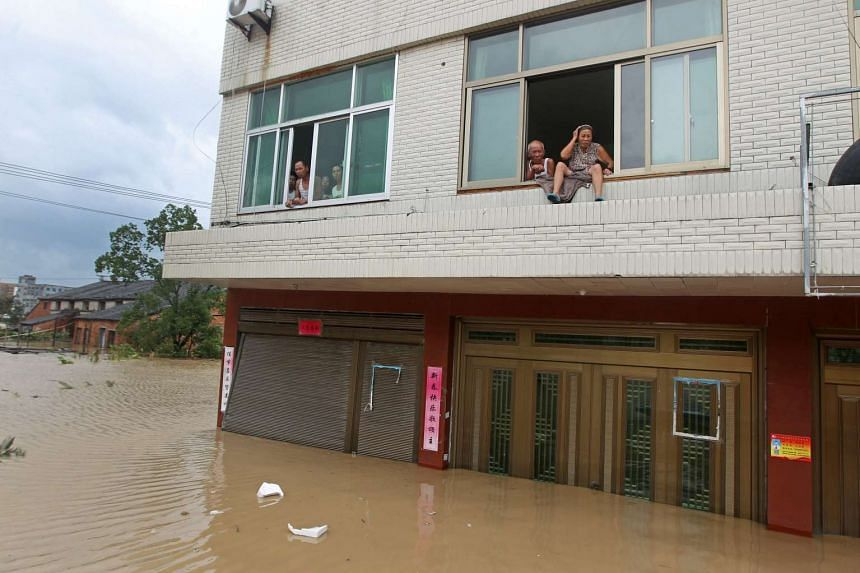 Residents looking out from a house while trapped by the flood in Pingyang county in east China's Zhejiang province on Aug 9, 2015.