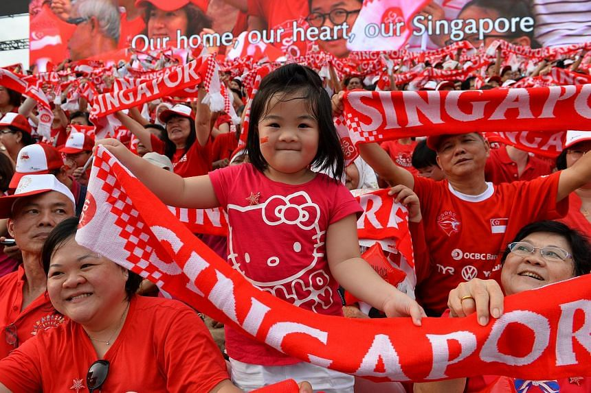 The crowd celebrating and waving banners at the National Day Parade at the Padang on Aug 9, 2015.