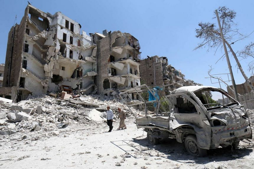Syrian men walk amidst the rubble and debris in the Qadi Askar district of the northern Syrian city of Aleppo on July 5 this year. Syrian rebels battled are battling ISIS extremists in northern areas of the country.