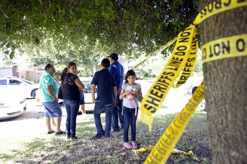 Neighbours gather behind police barrier tape at the scene of a shooting during which eight people were killed, in Houston, Texas on Sunday. Eight people, five of them children, were killed at a house in Houston and a suspect in the shooting surrender