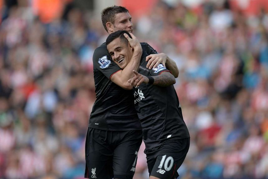 Liverpool's Brazilian midfielder Philippe Coutinho celebrates with Liverpool's English midfielder James Milner (left) after scoring the opening goal of the English Premier League football match between Stoke City and Liverpool at the Britannia Stadiu