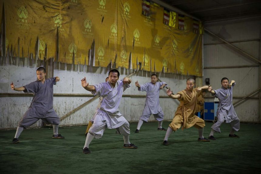 Several monks perform kung fu for tourists at the Shaolin Temple in Dengfeng, China, on July 31, 2015.
