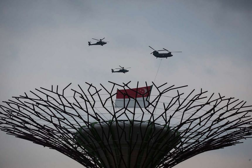 The traditional fly-past of the state flag, performed by a CH-47 Chinook helicopter escorted by two AH-64D Apache helicopters, passing over Gardens by the Bay. The aircraft flew over the Padang during the singing of the National Anthem