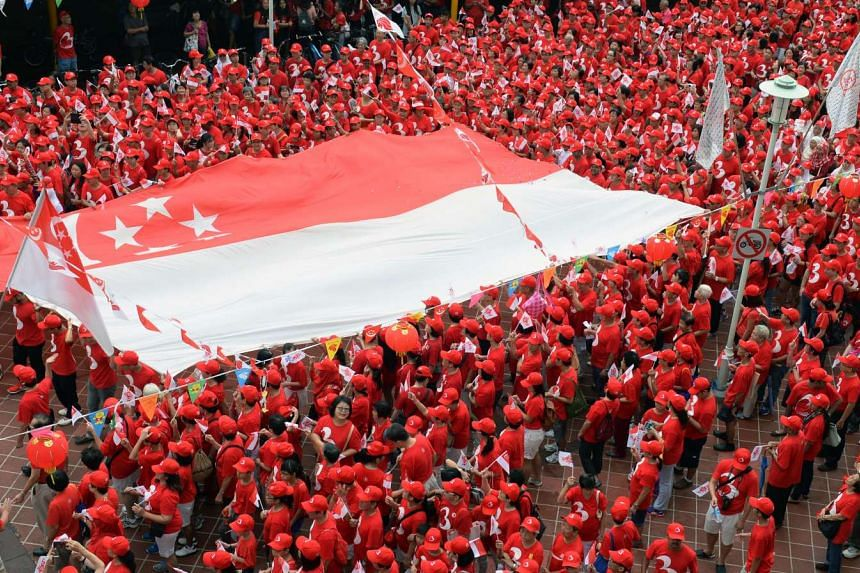 Waving their small flags on a balmy morning, these Bedok residents form an undulating sea of red as they march from Block 18, Bedok South Road, to the nearby community park. Several hands help to keep the giant Singapore flag aloft, in a show of unit