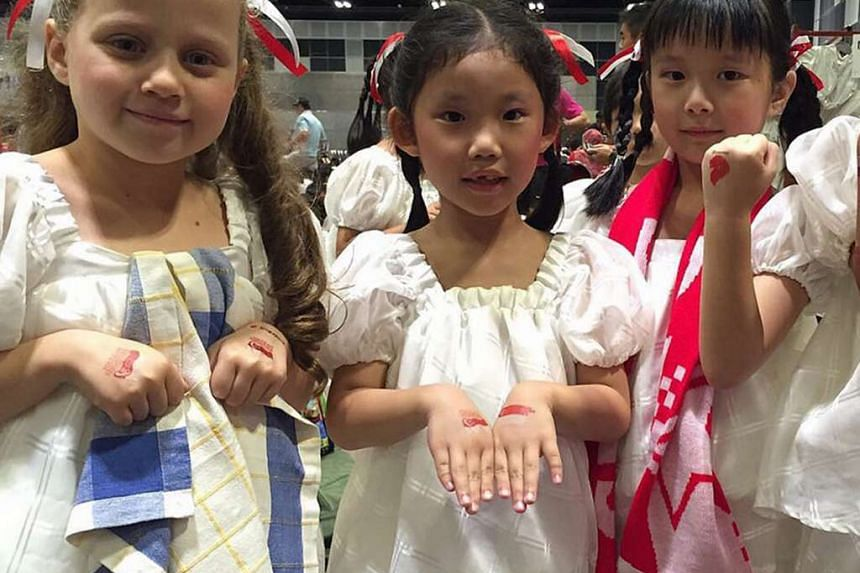 Anderson Primary School pupils (from left) Emilia Romanelli, Nico Lim and Wan En show off their temporary tattoos before appearing in celebrations at the Padang..