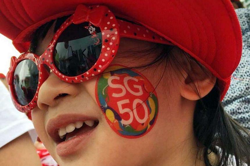 Evie Ong, three, enjoying the pre-parade entertainment through her sunglasses.
