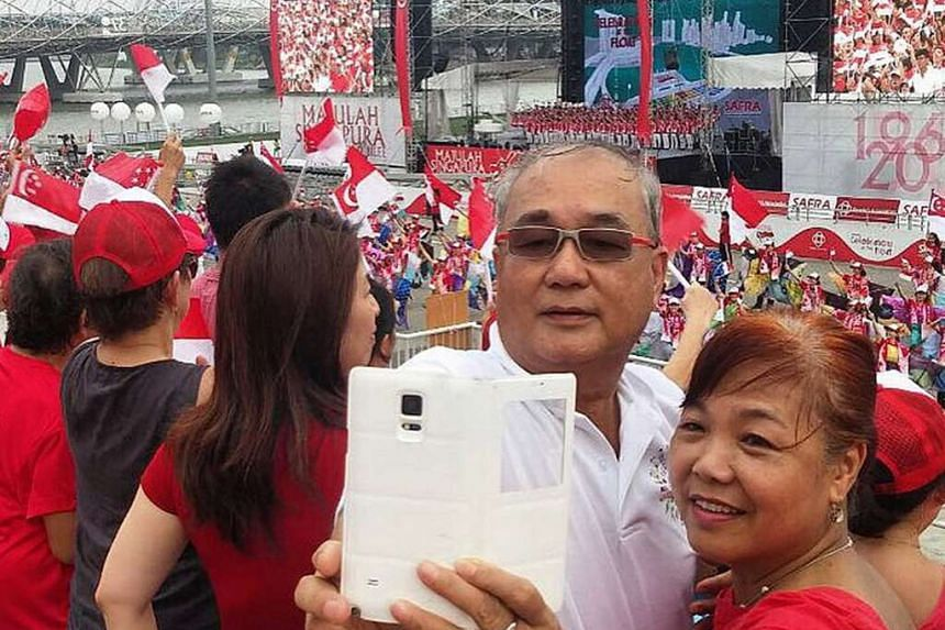 The crowd stands to sing along to Stand Up For Singapore and in the midst of the excitement, one couple seizes the moment to snap a wefie.