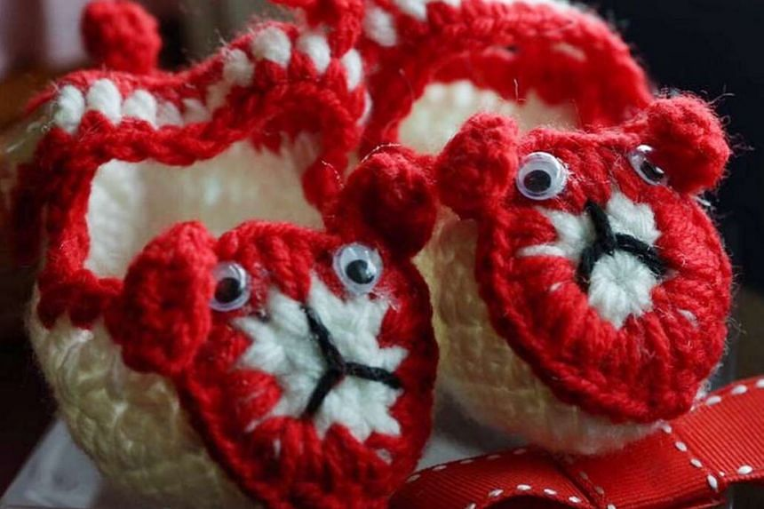 SG50 booties knitted by pioneer A. Prasad are given to the parents of jubilee babies Low Yu Qing and Ryker Jedd Ng, both of whom arrived at midnight on Aug 9.