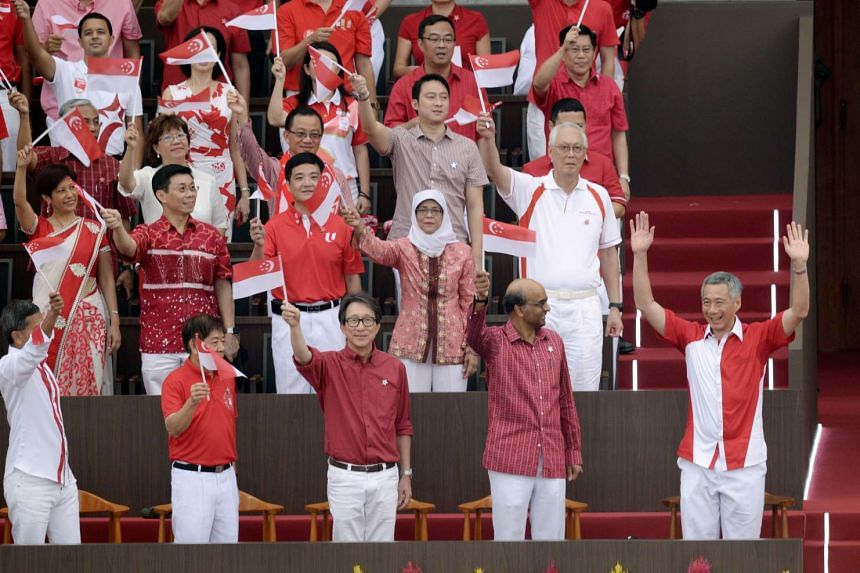 President Tony Tan Keng Yam, on the Presidential Ceremonial Vehicle, waving to spectators as the vehicle made its way around the arena. A beaming Prime Minister Lee Hsien Loong (above) waving to the crowd before taking his seat with members of the Ca