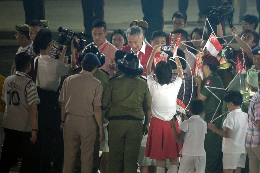 Prime Minister Lee Hsien Loong thanking participants for a job well done at the end of the National Day Parade. Earlier, crowds in the stands waved banners and flags as artists belted out national songs.