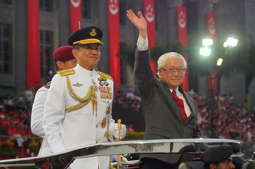 President Tony Tan Keng Yam (above), on the Presidential Ceremonial Vehicle, waving to spectators as the vehicle made its way around the arena. A beaming Prime Minister Lee Hsien Loong  waving to the crowd before taking his seat with members of the C