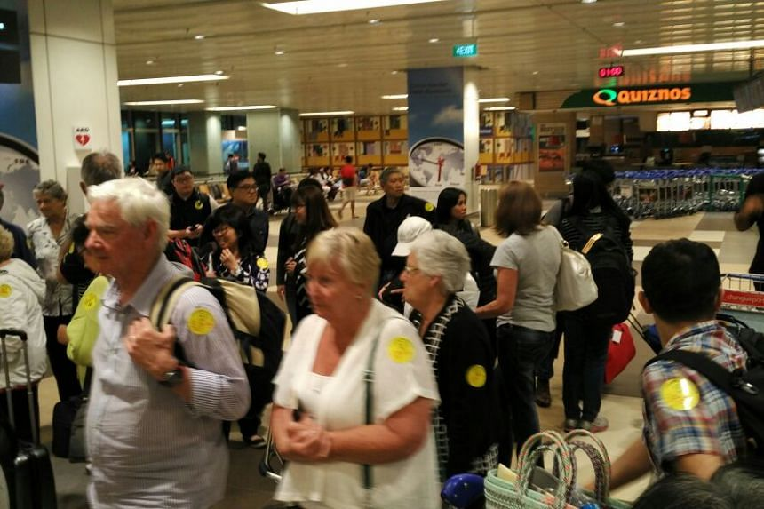 Passengers of Qantas flight QF36 waiting in vain for the plane to arrive at Changi Airport Terminal 1 on Sunday (Aug 9) night.
