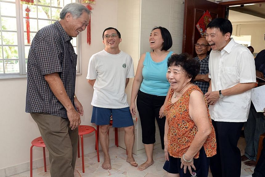 Defence Minister and Bishan-Toa Payoh GRC MP Ng Eng Hen (far left) and potential new PAP candidate Chee Hong Tat (left, in white shirt) sharing a laugh with resident James Tan (in blue shorts), 34, and his family during a house visit in the Balestier