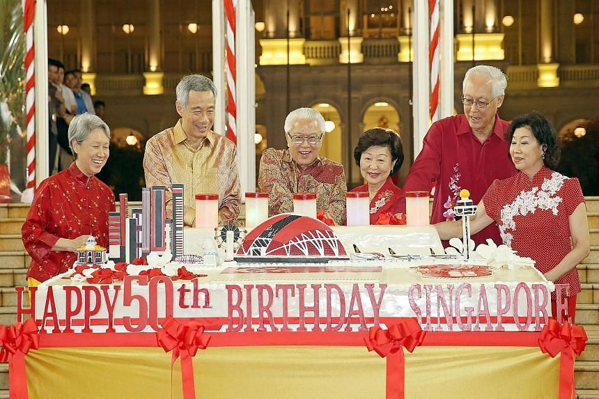 President Tony Tan Keng Yam and his wife, Mrs Mary Tan (centre) are joined by Prime Minister Lee Hsien Loong and his wife, Madam Ho Ching (left), and Emeritus Senior Minister Goh Chok Tong and his wife, Madam Tan Choo Leng (right), in cutting a giant