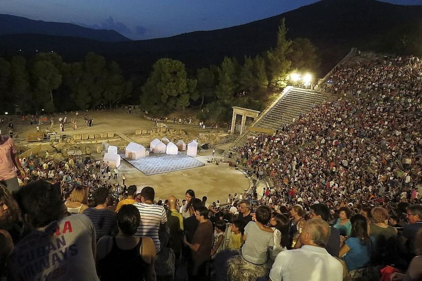 Spectators pack the ancient Greek amphitheatre of Epidaurus for a performance of Aristophanes' play Ecclesiazusae, or The Assembly Women.