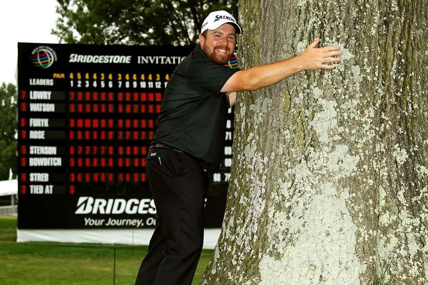 Shane Lowry rewarding the tree near the 18th green that knocked his ball onto the green with a hug. The shot helped the Irishman win the World Golf Championships - Bridgestone Invitational with a score of -11.