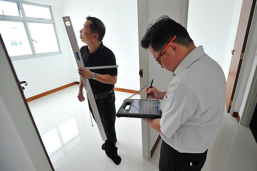 Building and Construction Authority assessors Simon Yee (right) and John Koh inspecting a flat in Fernvale Street.