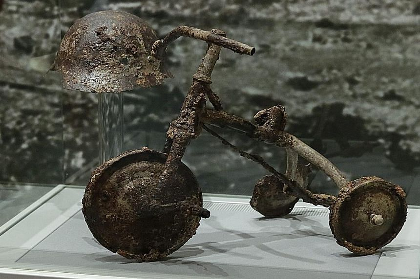 Poignant reminders: A helmet and tricycle which once belonged to three-year-old Shinichi Tetsuya, who was killed by the atomic bomb while on the tricycle some 1.5km from the hypocentre. The tricycle, which was damaged, is on display at the Hiroshima