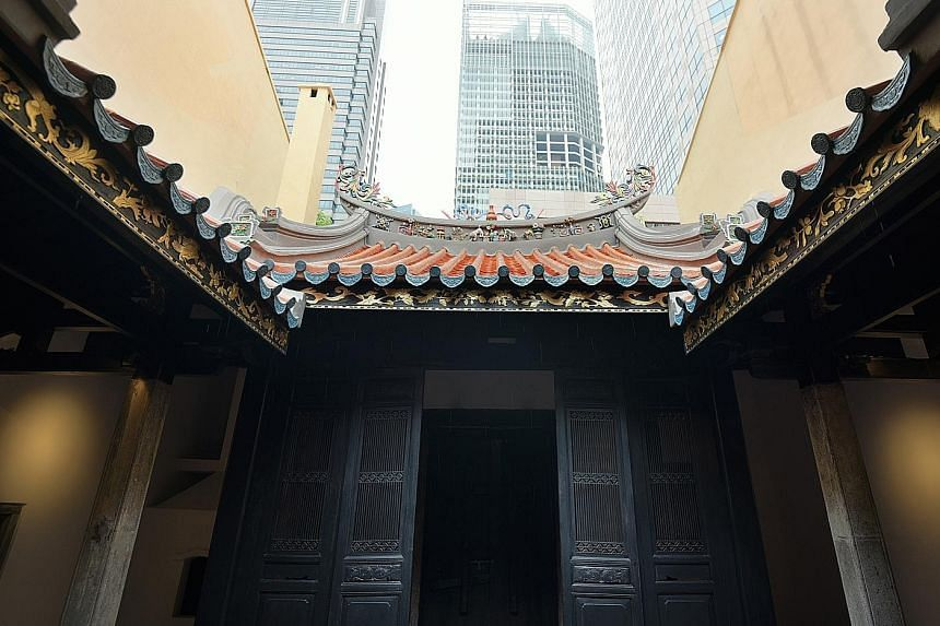 The 1824 structure (above) serves as a museum and a thoroughfare. Experts repaired and repainted the ceramic phoenix and dragon emblems on the roof's ends (left). Signs highlight features such as its life-size door gods (far left).