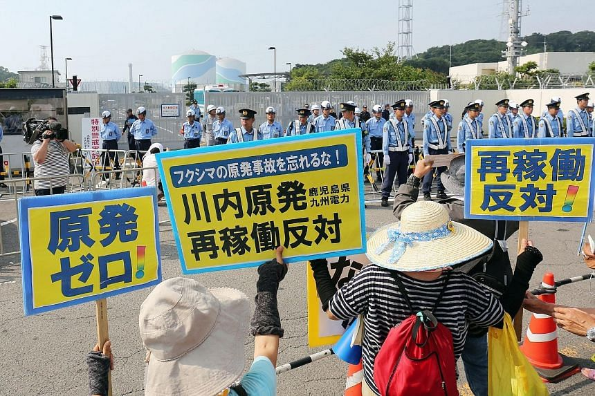 Protesters rallying with posters yesterday against the restart of a nuclear reactor at Kyushu Electric Power's Sendai power plant in Kagoshima prefecture. Japan is set to restart the mothballed reactor today, the first time in two years, as anti-atom