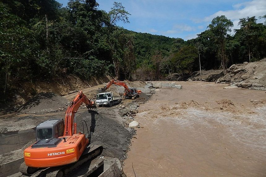 Workers clearing the silt after heavy mudflow into a water intake point in Sabah's Sungai Liwagu forced it to shut down. Heavy mudflows from Mount Kinabalu continue to torment villagers, two months after an earthquake that killed 18 people. The mudfl