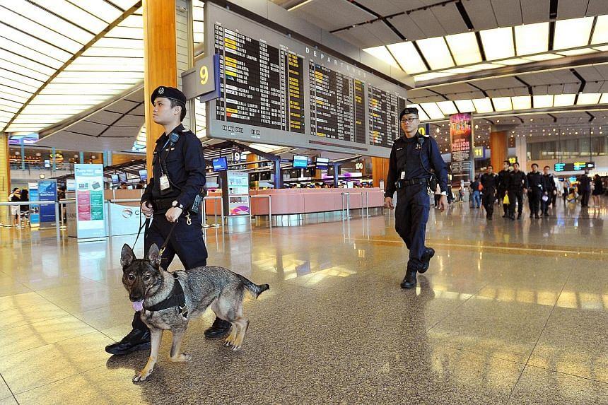 Staff Sergeant Joshua Lo, 32, seen handling German shepherd Kora, and Senior Staff Sergeant Koh Eng Ann, 37, patrolling Changi Airport's Terminal 2 on Saturday. The dogs sniff out drugs, firearms and bombs to keep Singapore safe. (Left) Staff Sergean