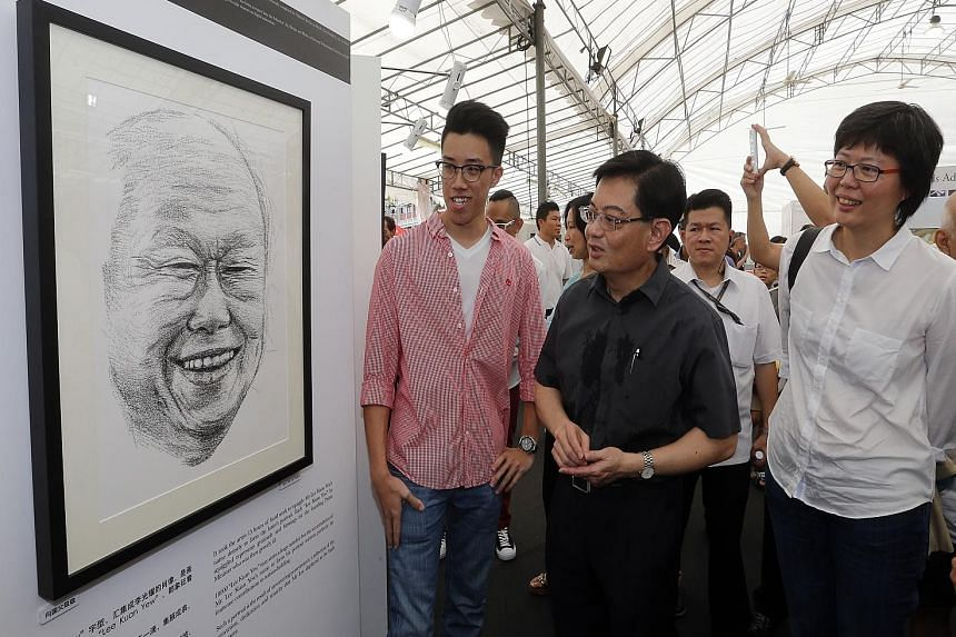 Above: Mr Heng Swee Keat (centre) viewing a portrait of Mr Lee Kuan Yew with artist Ong Yi Teck (left) and Lianhe Wanbao editor Lee Huay Leng. Left: A book on the outpouring of grief after Mr Lee died.