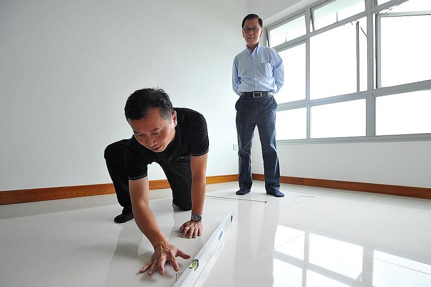 BCA assessor John Koh inspecting the floor of a new BTO flat in Fernvale Street. Conquas scores have been rising, said HDB.