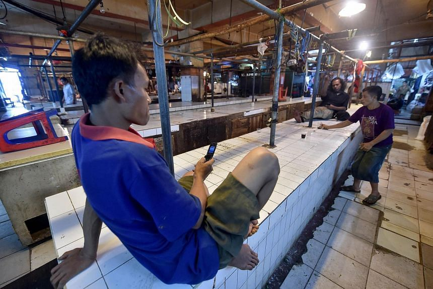 An Indonesian butcher looks at his phone in the near-empty meat section of a traditional market in Jakarta on Aug 11, 2015.
