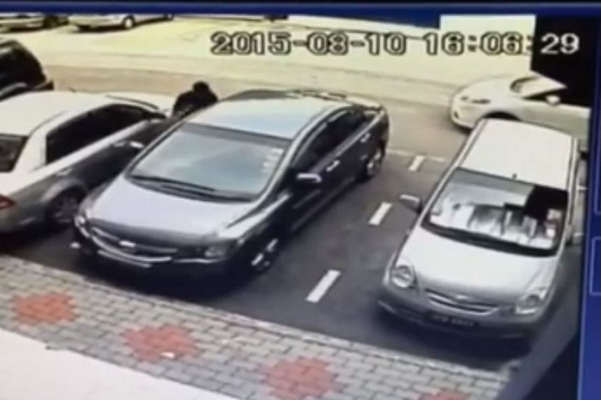 The thief, dressed in black, in the act of stealing Singaporean Nolan Khoo's Honda Civic at Tebrau City in Johor Baru on Monday (Aug 10).