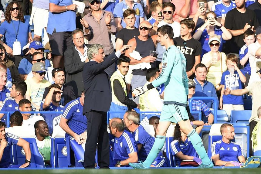 Courtois (right) leaves the pitch after being sent off in Chelsea's match against Swansea.