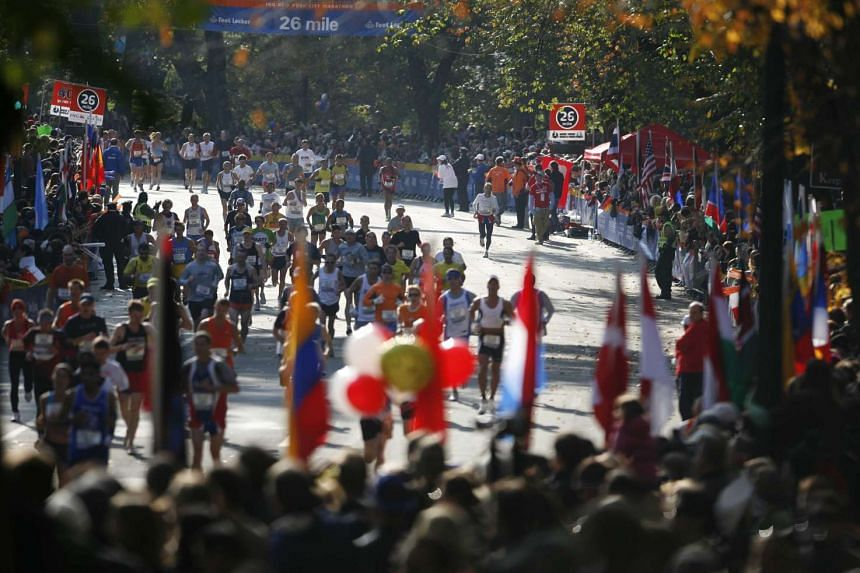 Crowds watch runners pass the 26-mile mark during the New York City Marathon in New York, on Nov 5, 2006.