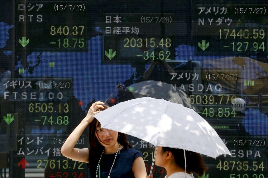 Women stand in front of a board showing market indices in Tokyo.