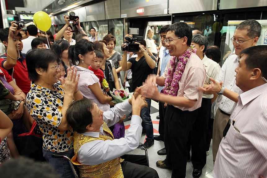 Commuters welcoming Minister for Transport Lui Tuck Yew at the Kent Ridge station on Oct 2, 2011.