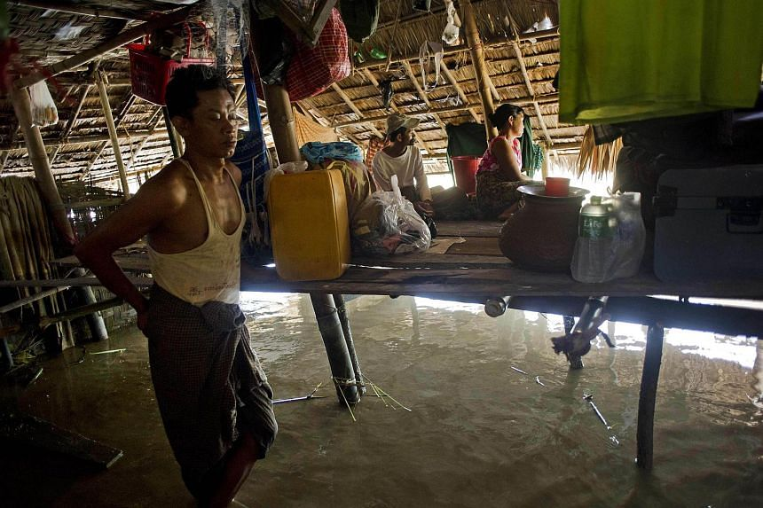 A resident stands in his partially submerged home as flooding hits the village of Kyaut Ye near the town of Hinthada in Myanmar's Irrawaddy region on Aug 10, 2015.