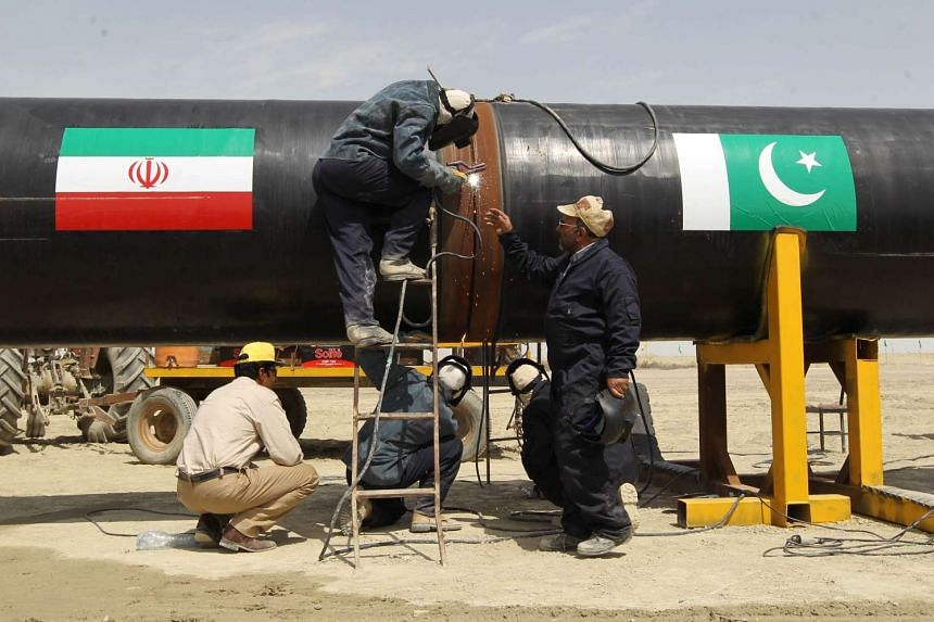 Iranian labourers work on a section of a pipeline - adorned with the flags of Iran (left) and Pakistan,  in the Iranian border city of Chah Bahar on March 11, 2013.