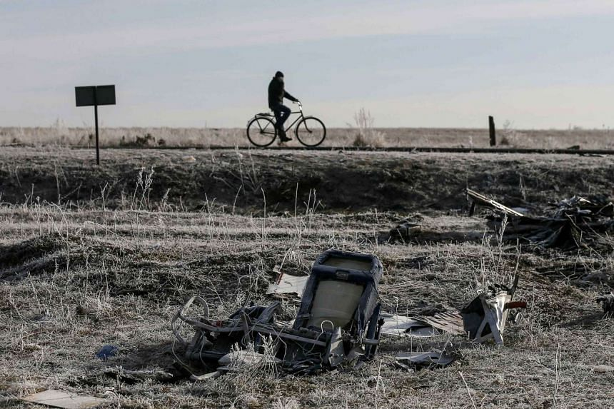 A man rides his bicycle past the wreckage of the Malaysia Airlines Flight MH17, near the village of Hrabove (Grabovo) in Donetsk.
